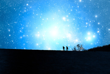 Silhouettes of two man on the top of the hill watching the stars.