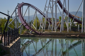 rollercoaster with artificial lake in amusement park