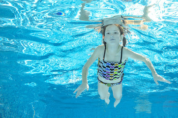 Child swims in pool underwater, happy active girl has fun in water