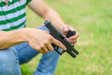 Gun man hand on green background