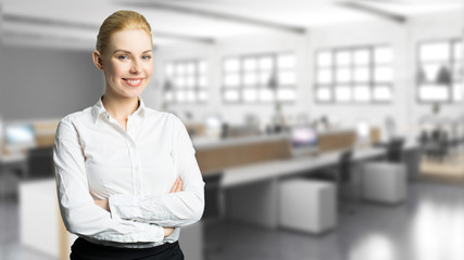 junge Geschäftsfrau vor Büro-Hintergrund mit vielen Computer-Arbeitsplätzen