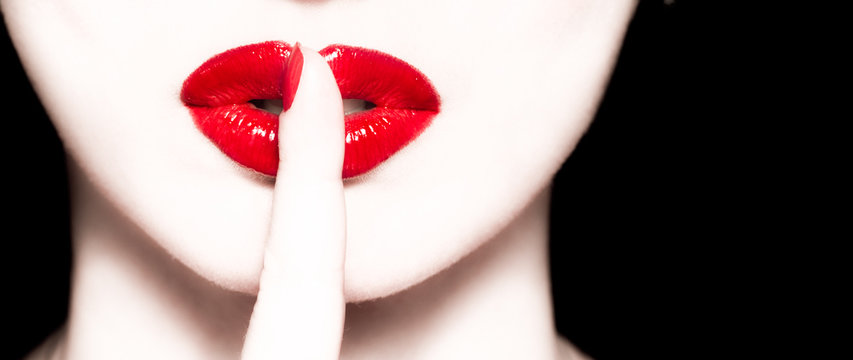 macro of lips with red lipstick and holding finger at mouth show