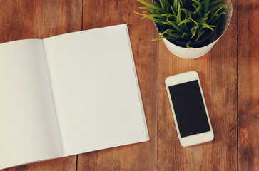 image of open notebook with blank pages next to smartphone