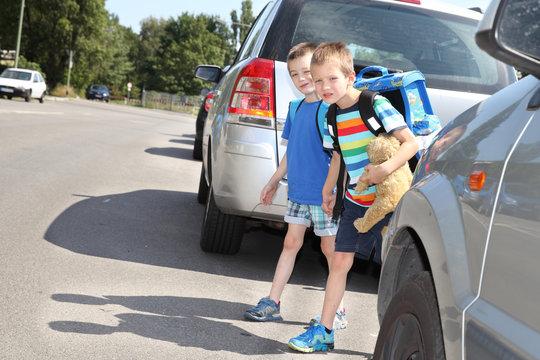 zwei Schulkinder beim überqueren einer Straße