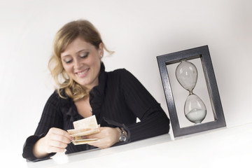 a manager count the gains and the passing time with an hourglass on the desk