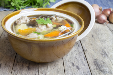 Thai soup recipe in a bowl on wooden
