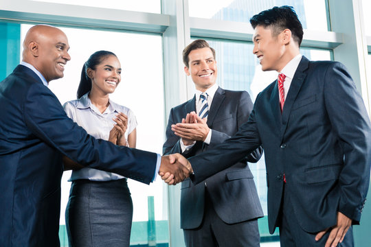 Business handshake in lofty office with city view