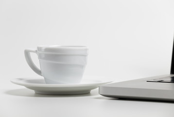 coffee cup and laptop on a white background