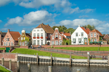 Facades of historic houses at Sielstrasse in the fishing harbour of Greetsiel, Lower Saxony, Germany