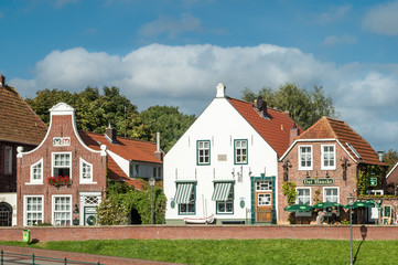 Facades of historic houses of Sielstrasse in the fishing harbour of Greetsiel, Lower Saxony, Germany