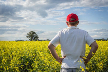 horizontal close up image of a man standing with his back to camera looking over his yellow canola field under a cloudy blue sky in the summer time.