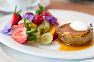 Warm, spicy baked apple with honey caramel sauce and bulgarian yoghurt, and fresh fruit decorated with edible purple flowers. Regional cuisine with a modern twist. Served in bed and breakfast inn.