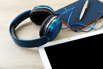 Headphones with tablet and notebook on wooden table close up