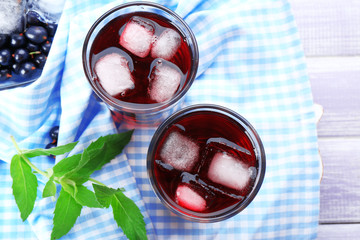 Glasses of fresh blackcurrant juice with ice cubes on checkered napkin on wooden table, top view