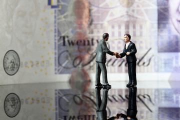 Miniature business figures note sterling. Miniature scale model business figures standing in front of a twenty pound note sterling.