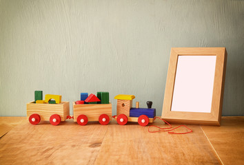 Wooden toy train over wooden table next to photo blank frame