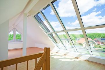 helles Dachgeschosszimmer mit großem Fenster