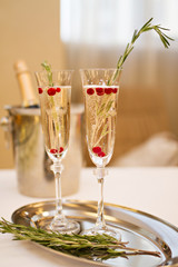 Two glasses of Champagne and rosemary branch on a table