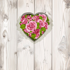Pink roses in a hole in the wooden boards in the form of heart