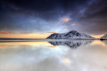 Sunset on Skagsanden beach surrounded by snow covered mountains reflected in the cold sea, Flakstad, Lofoten Islands, Arctic, Norway, Scandinavia, Europe