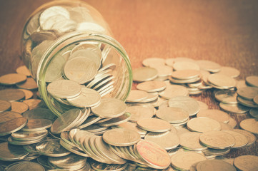 Coins spilling out of a glass bottle with filter effect retro vi