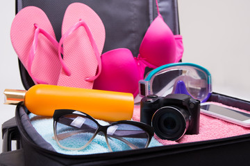 full travel suitcase with clothing and vacation items