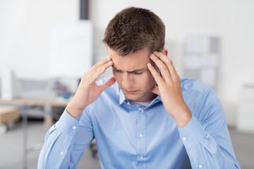 mann im büro mit kopfschmerzen