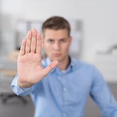 mann im büro streckt die hand nach vorne