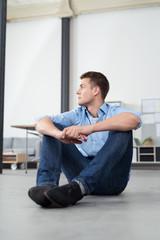 mann sitzt gelassen auf dem fußboden