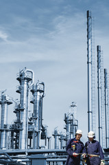 two oil workers with large oil and gas refinery industry