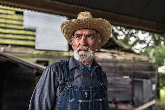 Old farmer standing in front of a rustic barn