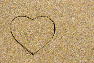 Heart shape engraved in a wet sandy beach