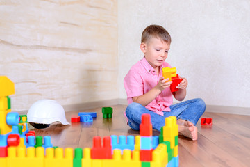 Cute cheeky young boy playing with building blocks