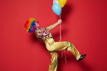 clown with balloons on red background