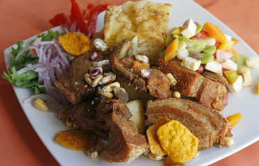 Peruvian food, Chicharron (fried pork) with potatoes, onion garnish, canchita.