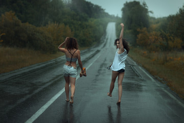 Two girls are on roadway in the rain.