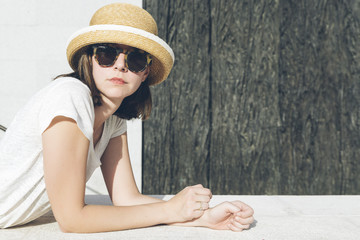 young casual girl wearing a hat and sunglasses
