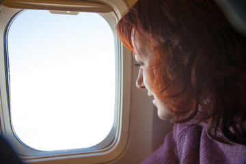 Traveling. Woman is sitting in the airplane.