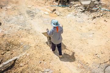 Construction worker pushing wheelbarrow on building site