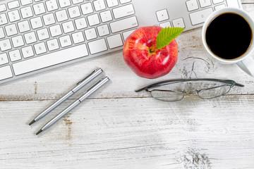 Computer keyboard with snack foods on top of old desktop