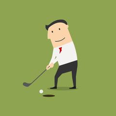 Businessman putting ball into a hole