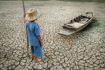 Boy looking to wooden boat on cracked earth.
