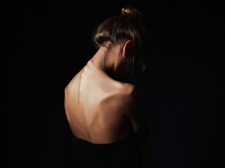 young woman with naked back over black background.sad girl