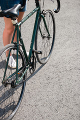 young woman in shorts near the city bike fixed gear