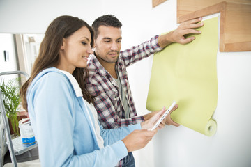 young couple choosing new pent paper with tablet pc