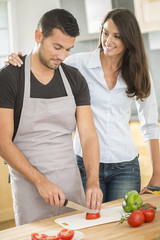 Young couple in kitchen prearing lunch