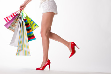 Girl in red shoes with shopping bags.
