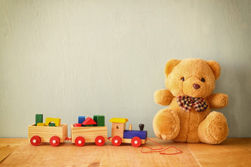 Wooden toy train and teddy bear over wooden floor