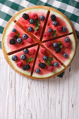 Watermelon decorated with berries vertical top view