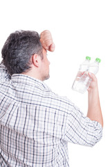 Thirsty man holding two bottles of cold water